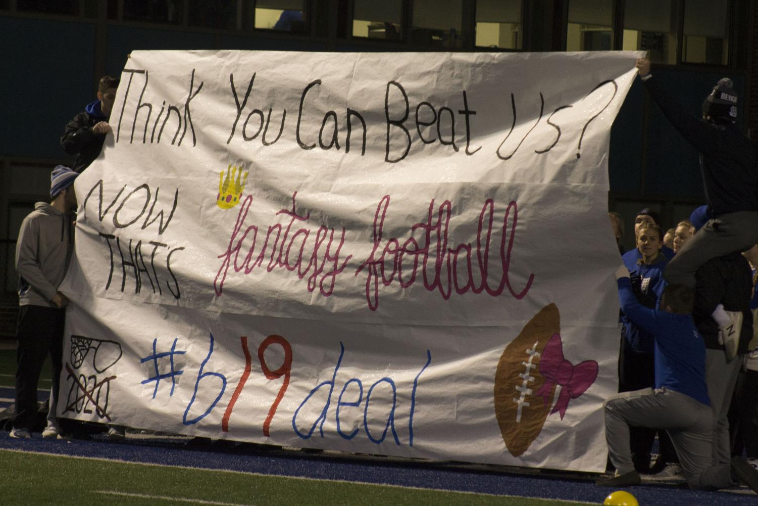 The seniors stand behind their sign before the game starts.