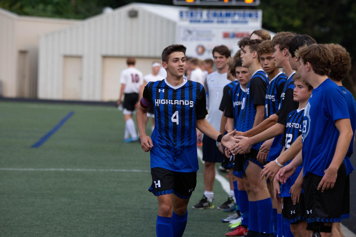 Senior Alex Ford high-fiving the soccer team before a game.