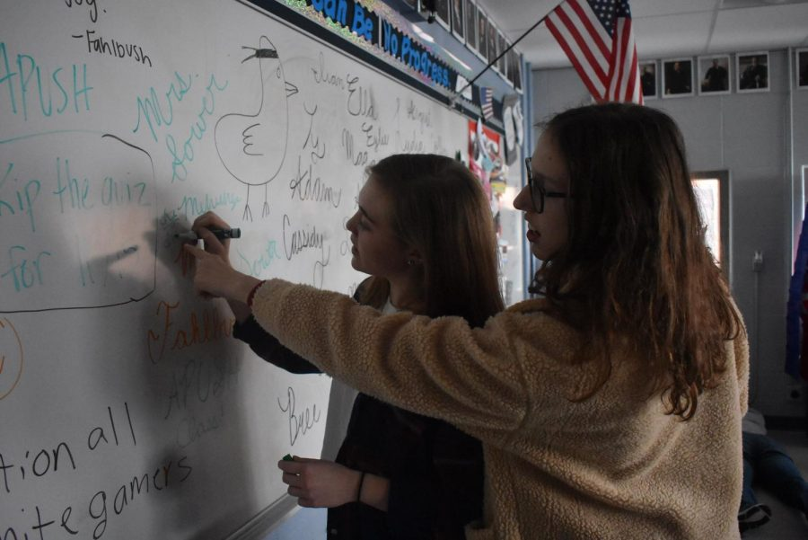 Juniors Mehryn Toole and Cassidy Perme draw on the white board.