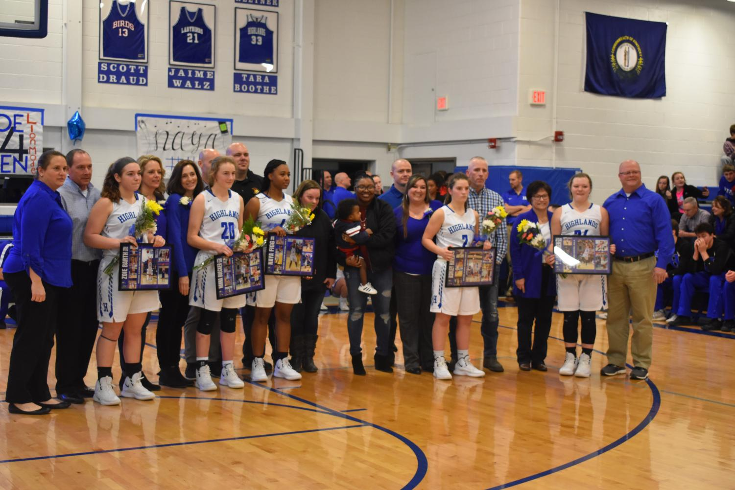The seniors on the girls basketball team stand together to wrap up the last home game of their high school career.