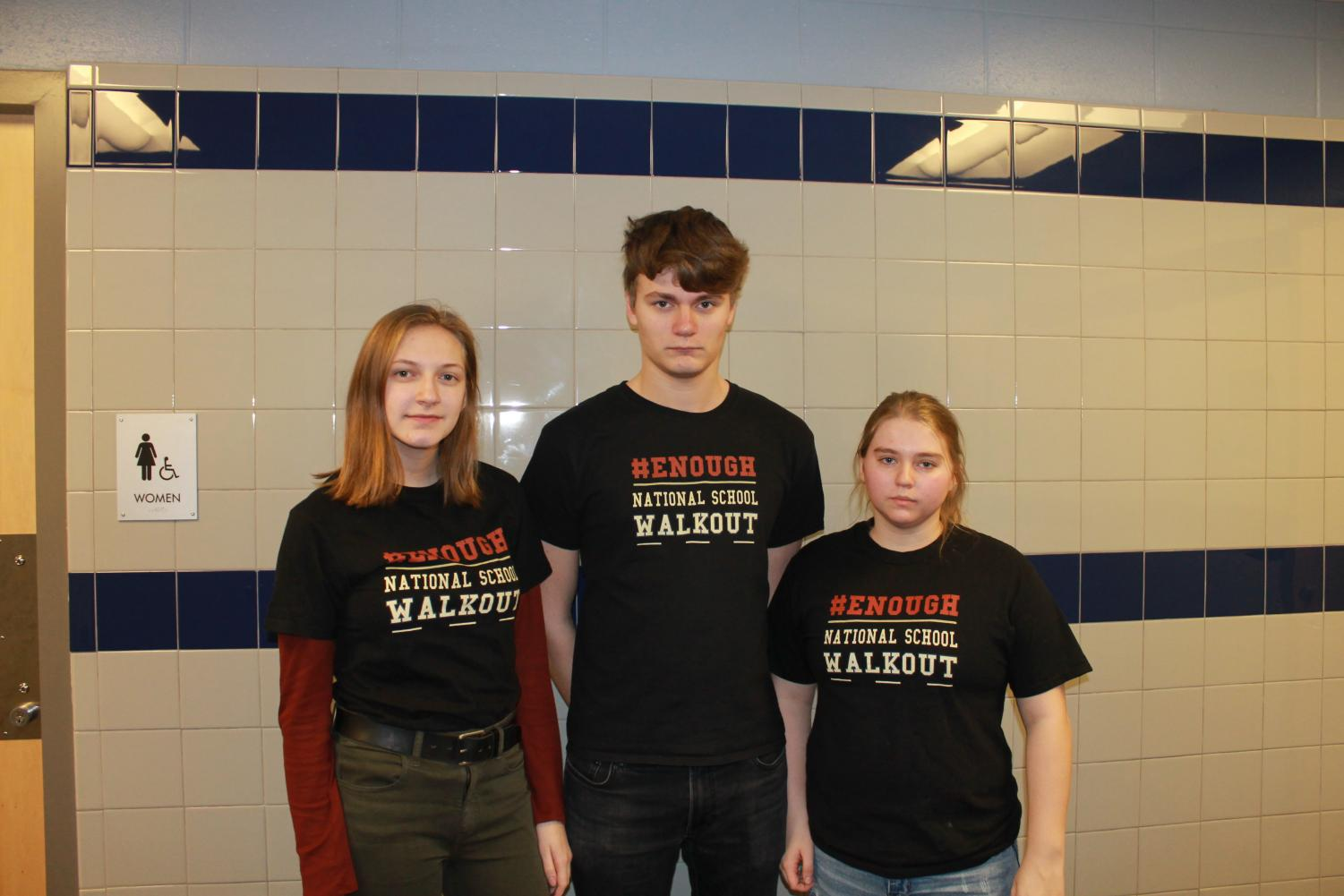 Sophomore Juli Russ and seniors Alex Harrison and Sydney Cooper wear their #Enough shirts to remember the lives lost during the Parkland shooting.