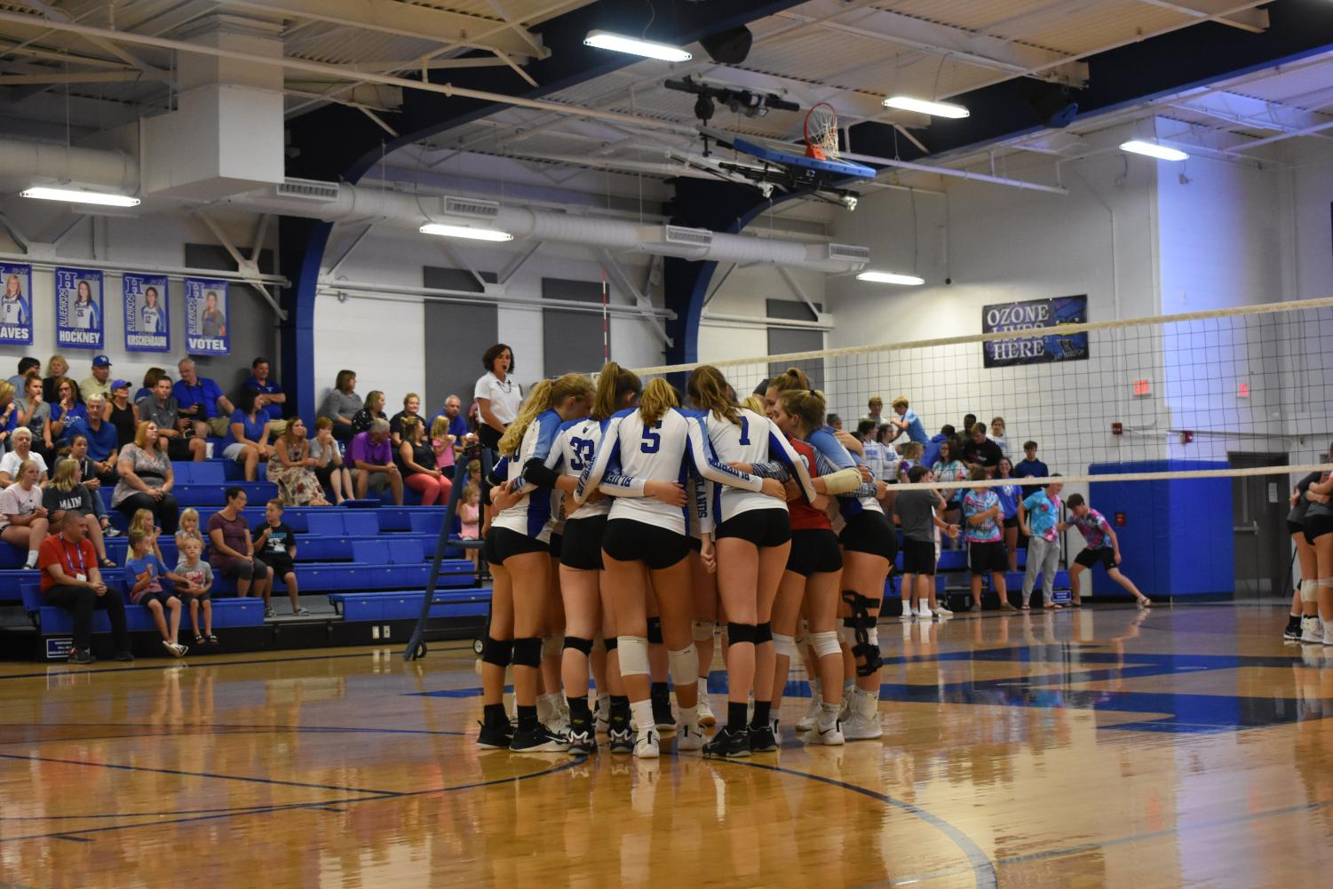 The Highlands girls varsity volleyball team huddles up before the start of the game.