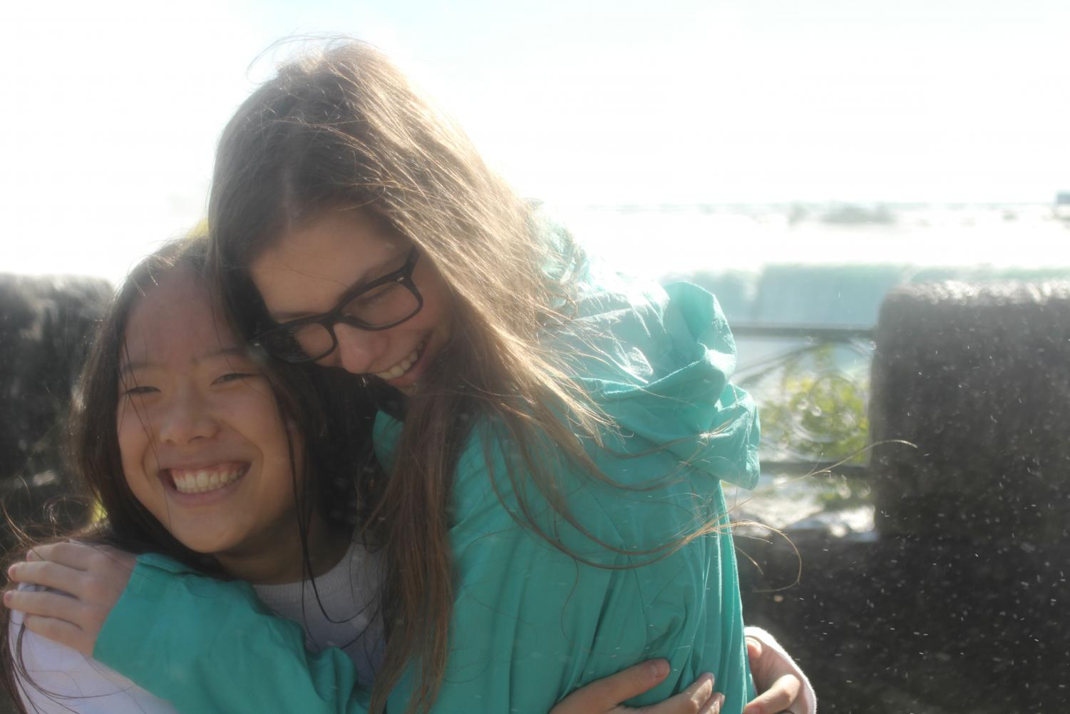 Juniors Sophia Knue and Jeanne DeGraaf huddle for warmth in the cool mist of NIagara Falls.