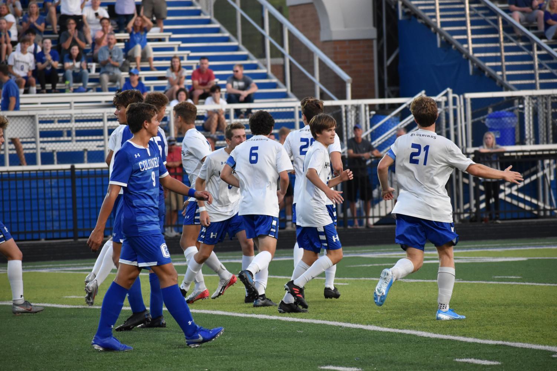 The boys varsity soccer team celebrates after a goal.