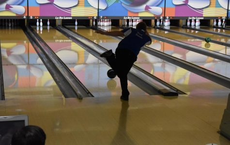 Senior Perry Daniels shoots for a split while warming up before the match