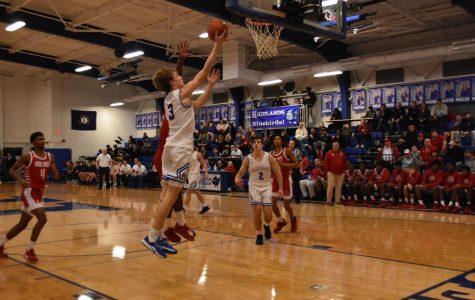 Junior Sam Vinson dunks the basketball during the Holmes game.