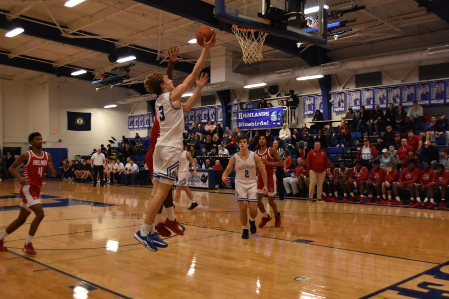 Junior Sam Vinson dunks the basketball during the Holmes game.