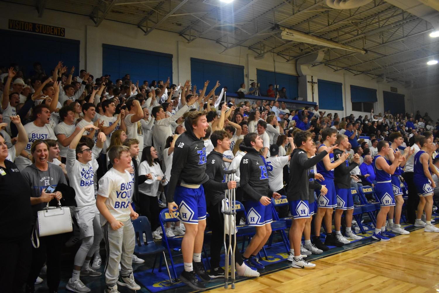 The O-Zone and players on the sideline celebrate following a dunk by Junior Sam Vinson.
