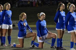Junior Faith Broering and senior Maggie Stieby take a knee during the National Anthem.