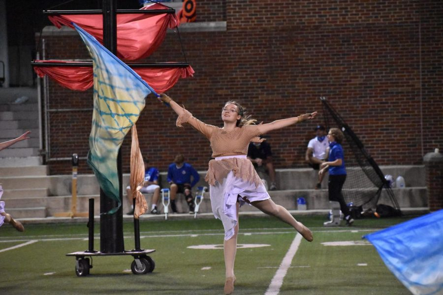 Senior Megan Benzing, guard member, spins her flag at the halftime performance for the football game on October 9.