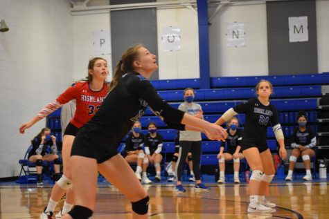 Senior Laura Winkler digs at the volleyball to keep the game in play.