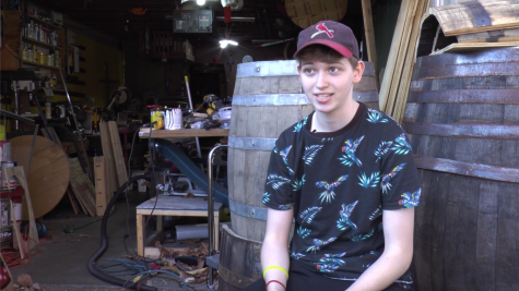 The owner of Scrap Wood Syd, Syd Bredwell, sits in front of her woodworking area.