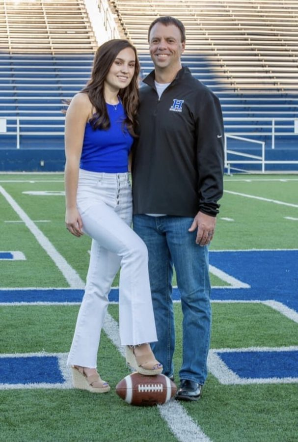Kenzie and Brian Weinrich pose for a picture on the football field where it all started.
