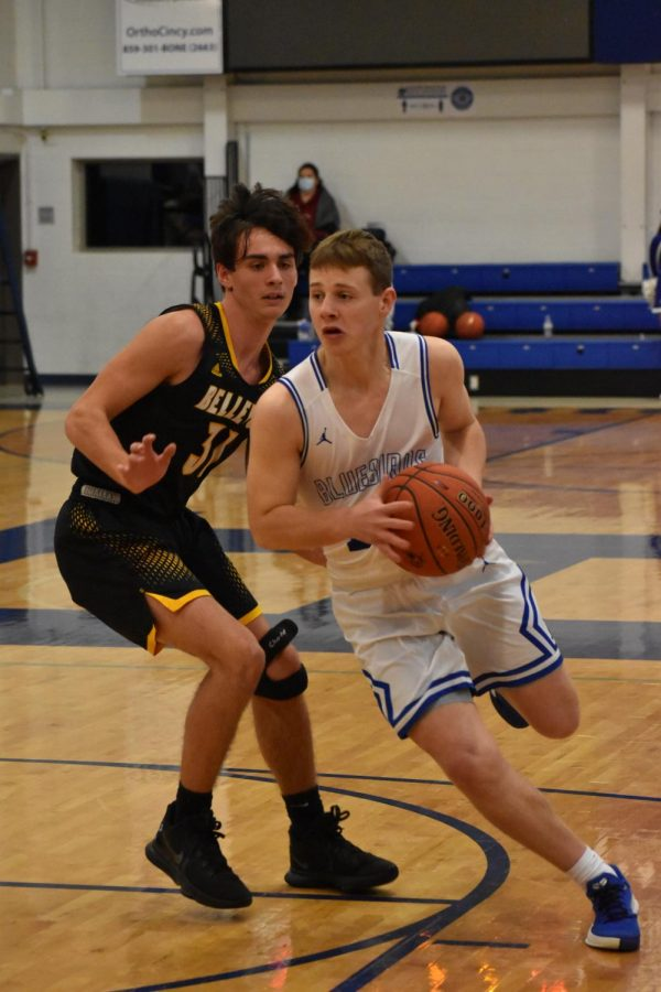 Junior Abe Hills dribbles past the opposing Tiger as he goes in for a basket.