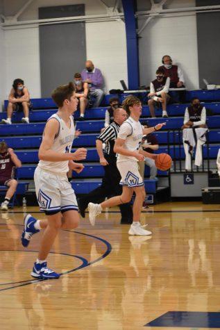Seniors Luke Muller and Sam Vinson run down the court toward the basket.