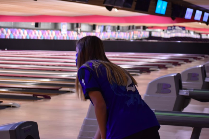 Senior Greta Noble, a new bowler this year, pulls a bowling ball from the rack in preparation for her turn on the lane.
