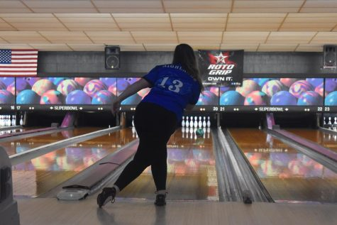 The anchor of the team, Senior Abby Bach, rolls the bowling ball down the lane.