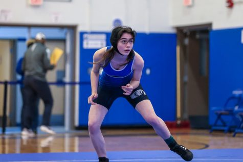 A wrestler circles the mat, eyeing her competition.  Photo courtesy of DWC Photo.