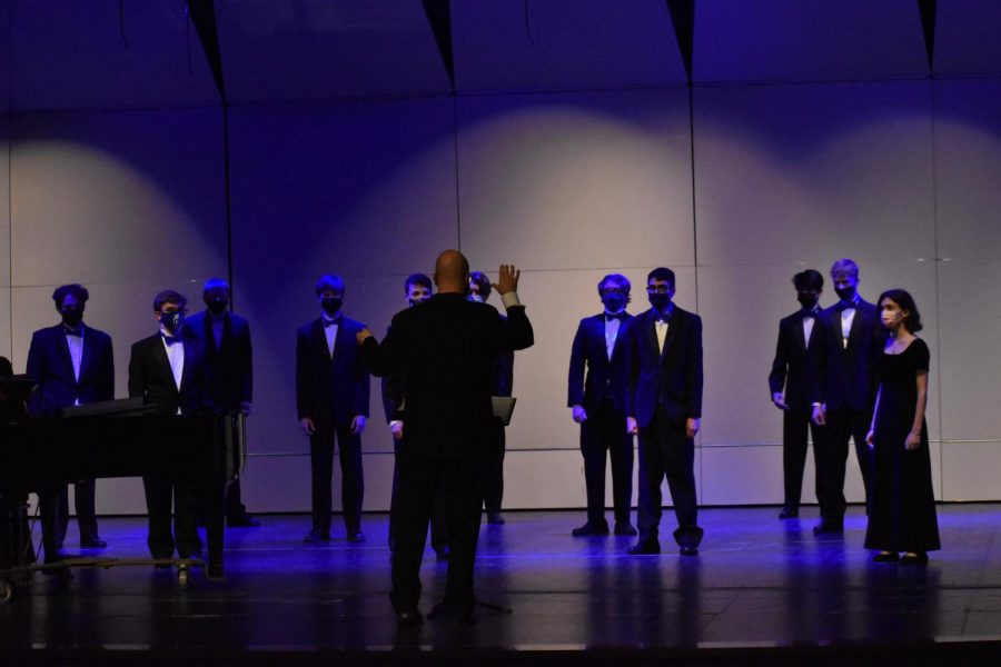 The chamber choir stands at attention for Young.