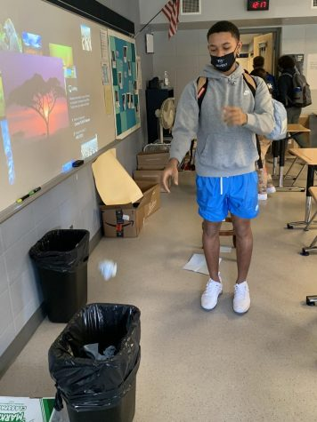 Freshman Ty Boler shoots his paper towel into the trashcan as class ends.