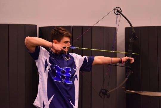 Senior Ethan Stuart, Archery Team co-captain, draws his bow back and aims towards the target.