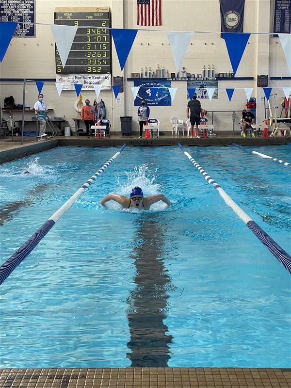 Sophomore Belle Bryant swims the 100 meter butterfly at a swim meet.