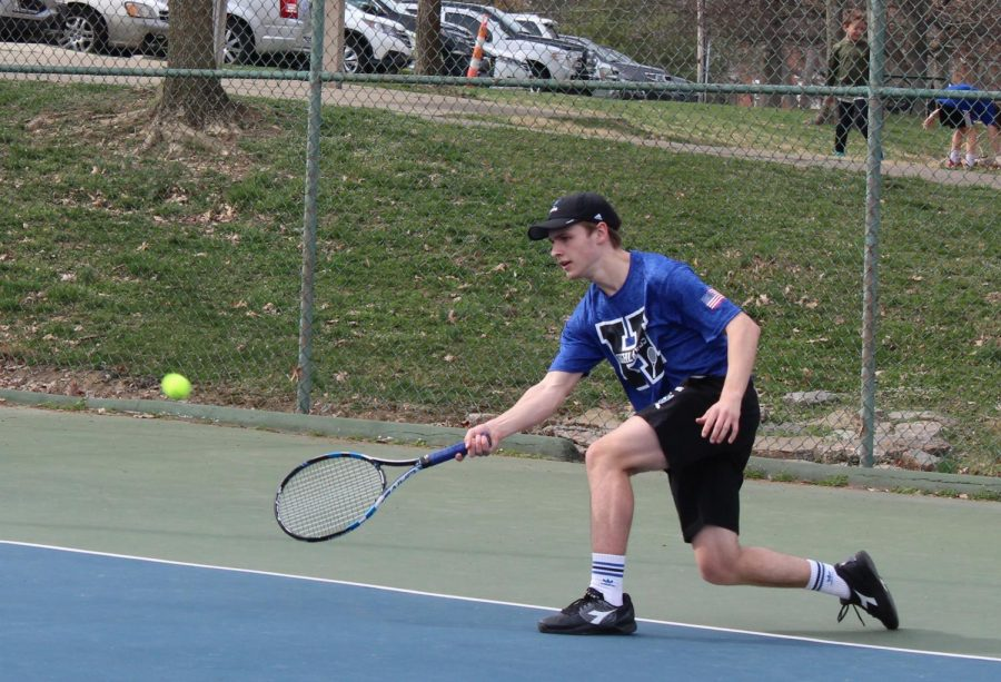 Senior Peter Laskey extends his arm to reach the tennis ball for a return.