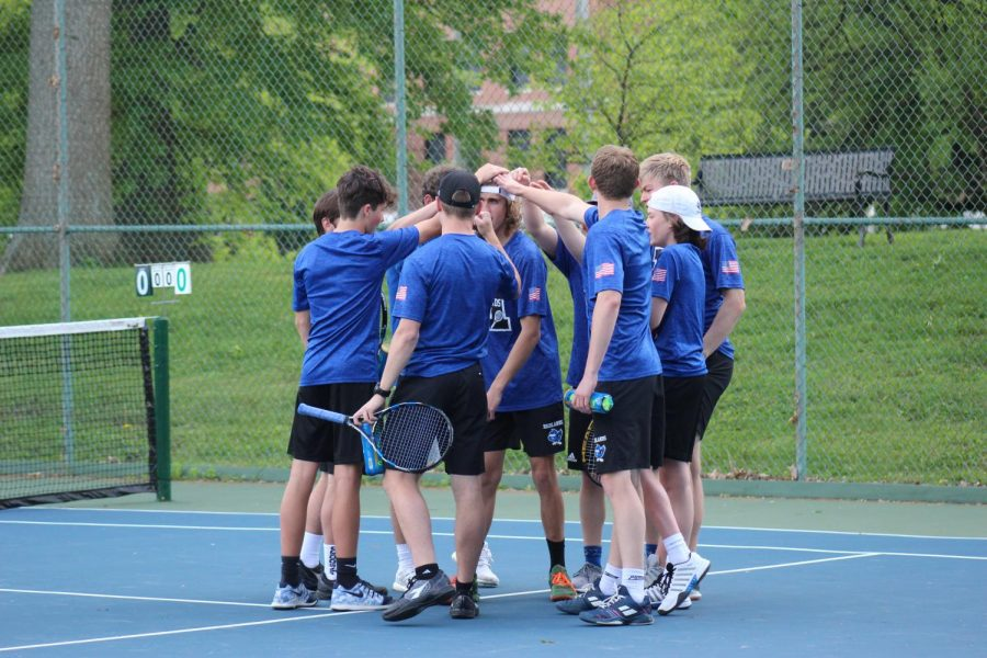 The boys' tennis team gather together for a pregame huddle to discuss strategy.