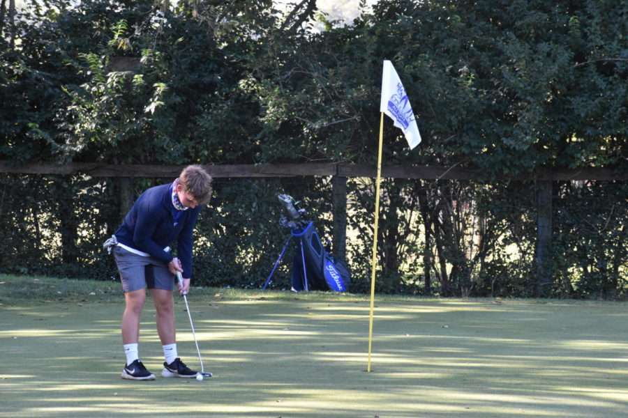 During the 2020-2021 golf season, then Junior Jack Schneider prepares to hit the golf ball into the hole.