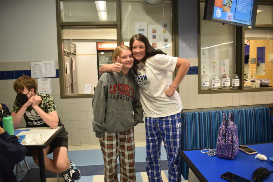 Juniors Kennedy Baioni and Brynn Syther smile together wearing matching plaid PJ pants.