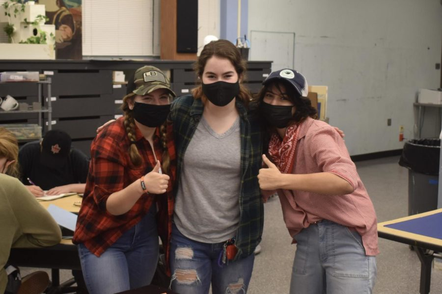 Seniors Brynn Shannon, Mackenzie Opitz, and Erica Kruse pose together in their flannel outfits.