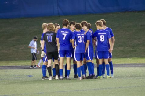 Boys Varsity soccer birds go in for a team huddle after the first half of the game.