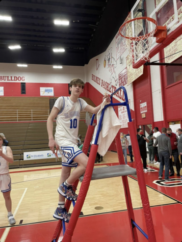 Senior Zach Barth poses as he cuts the net after winning region at Holmes High School.