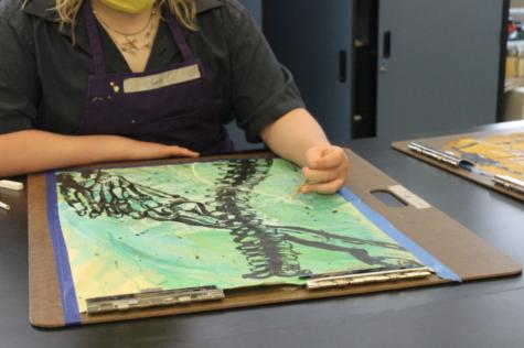 Junior Lela Grillot shows off her art work.