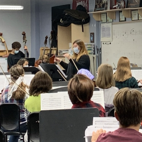Lubitza Hershberger conducts the class while they play their instruments.