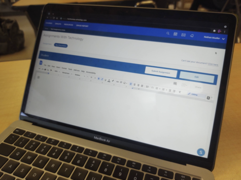 A MacBook Air displaying a Schoology page with a student assignment.